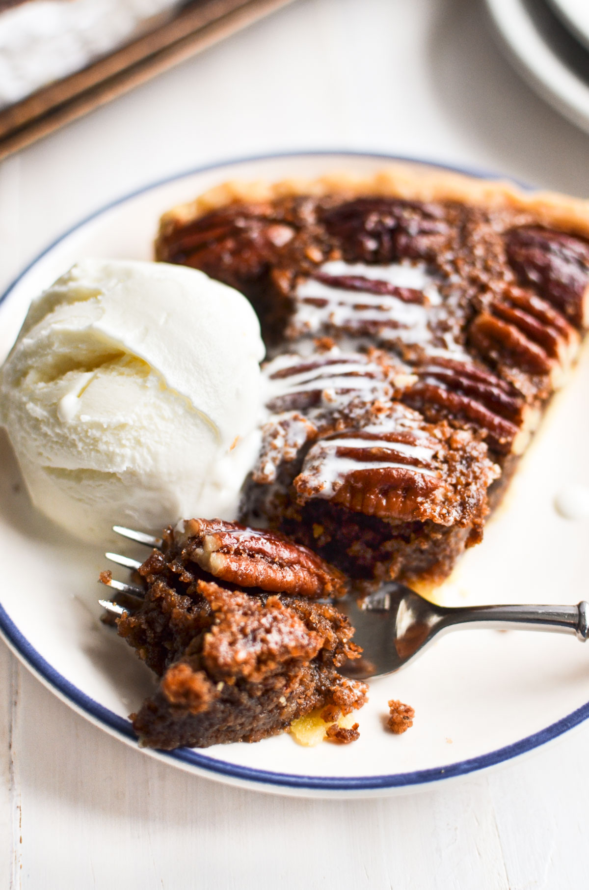 A piece of pecan pie with ice cream and fork