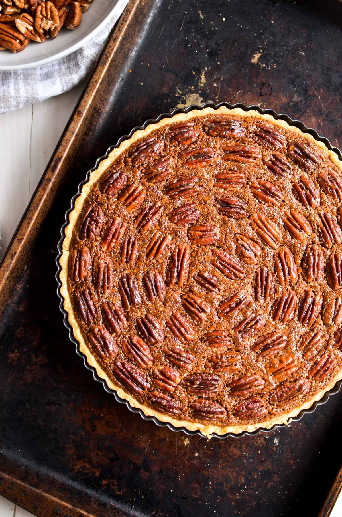 Maple frangipane pecan pie on a rusty baking sheet