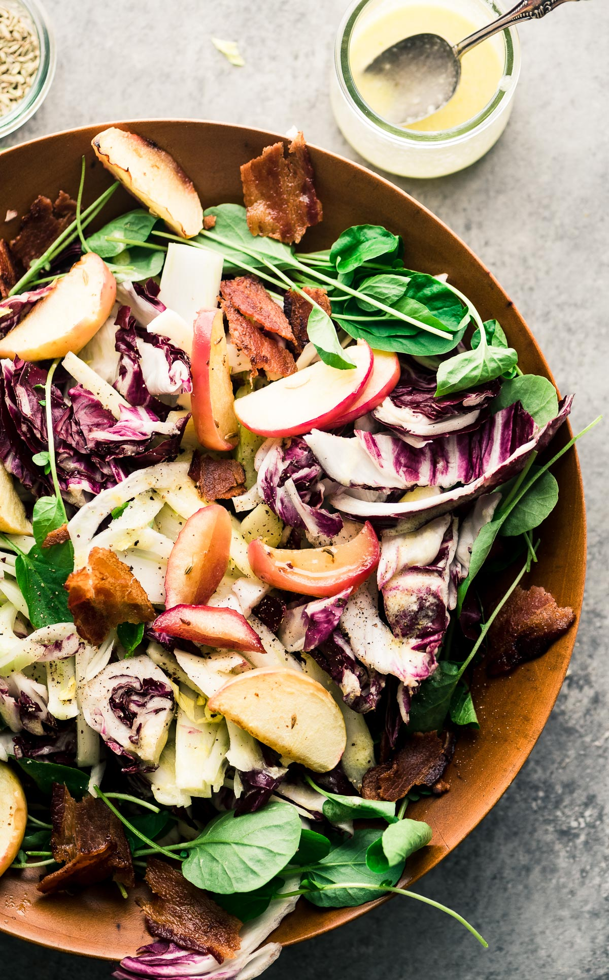 roasted apple and radicchio salad in a bowl with dressing