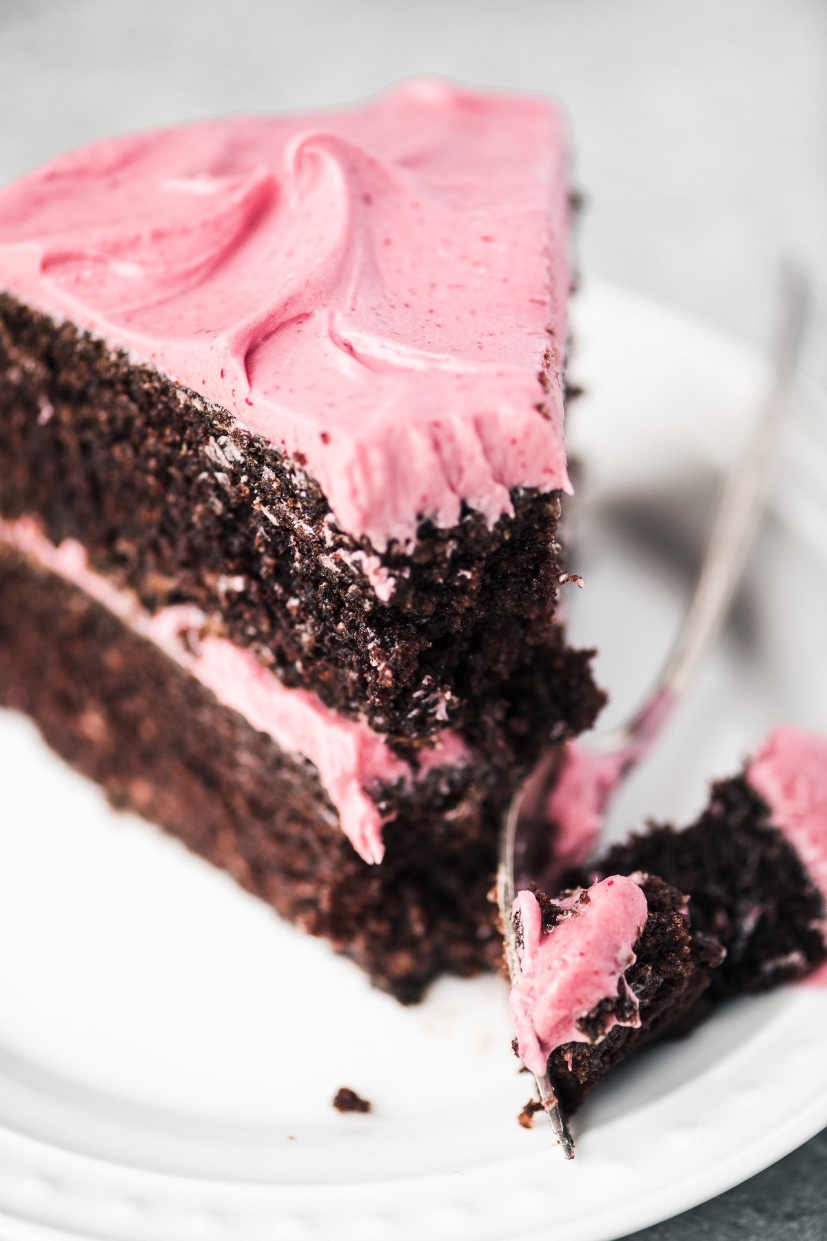 Taking a bite of chocolate cake with cranberry buttercream