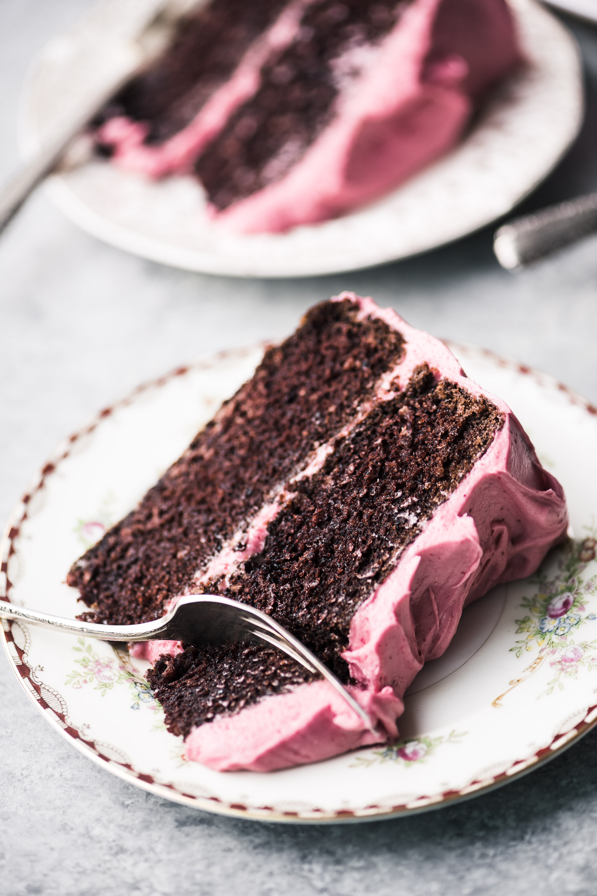 slices of chocolate layer cake with cranberry buttercream on small plates