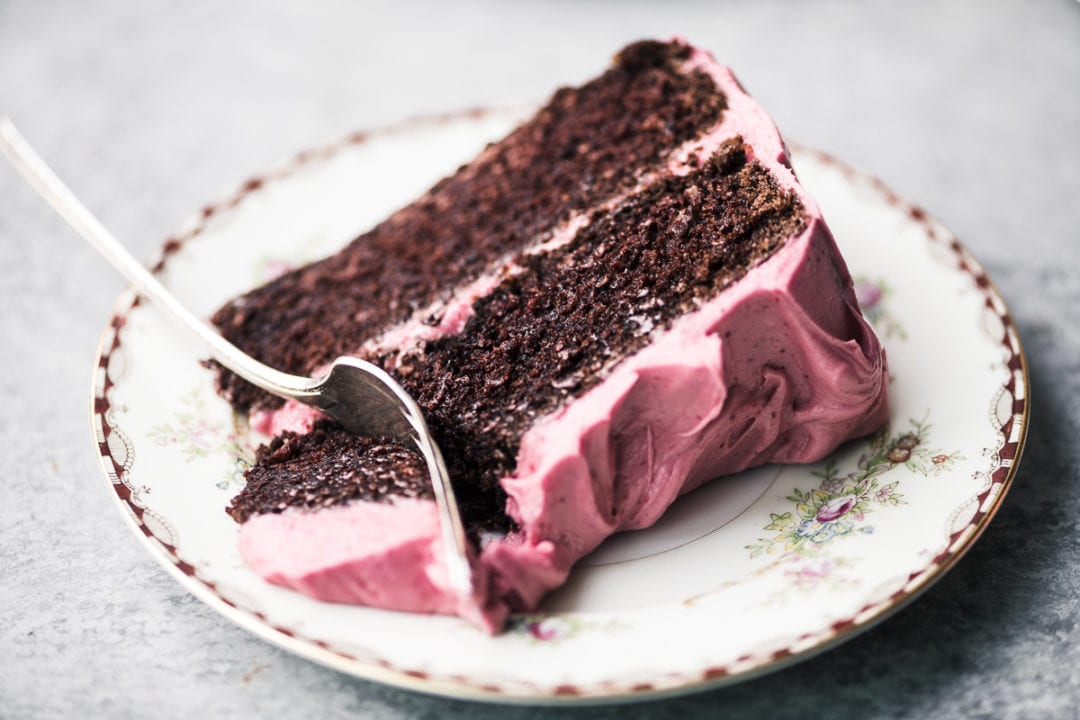 a slice of chocolate cake with cranberry buttercream