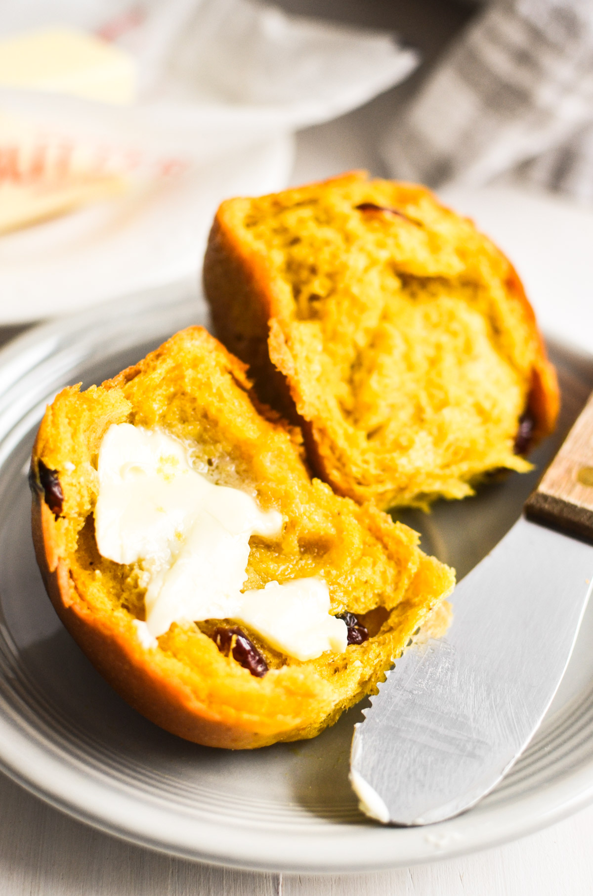 a cranberry pumpkin dinner roll, split, with butter