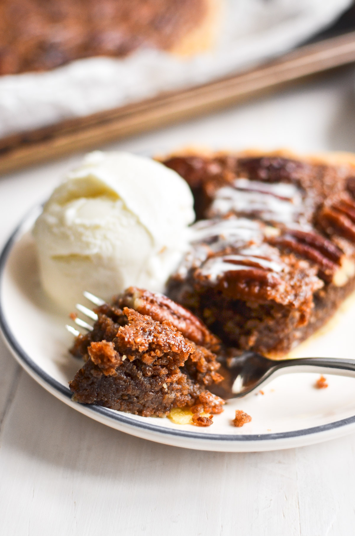 a slice of maple frangipane pecan pie with ice cream