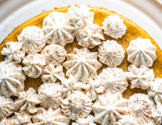 pumpkin spice cheesecake topped with piped whipped cream and nutmeg