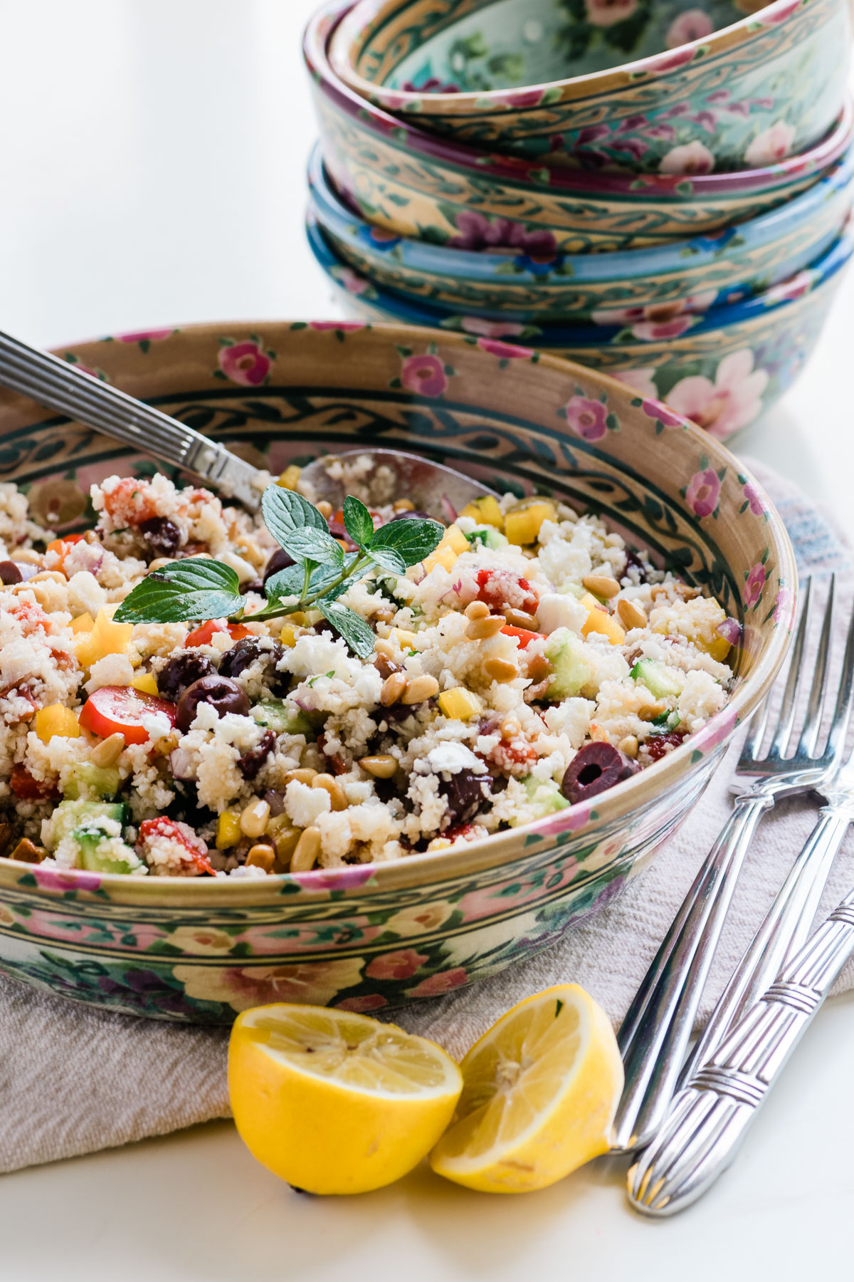 A cauliflower rice salad in floral bowls, with lemons