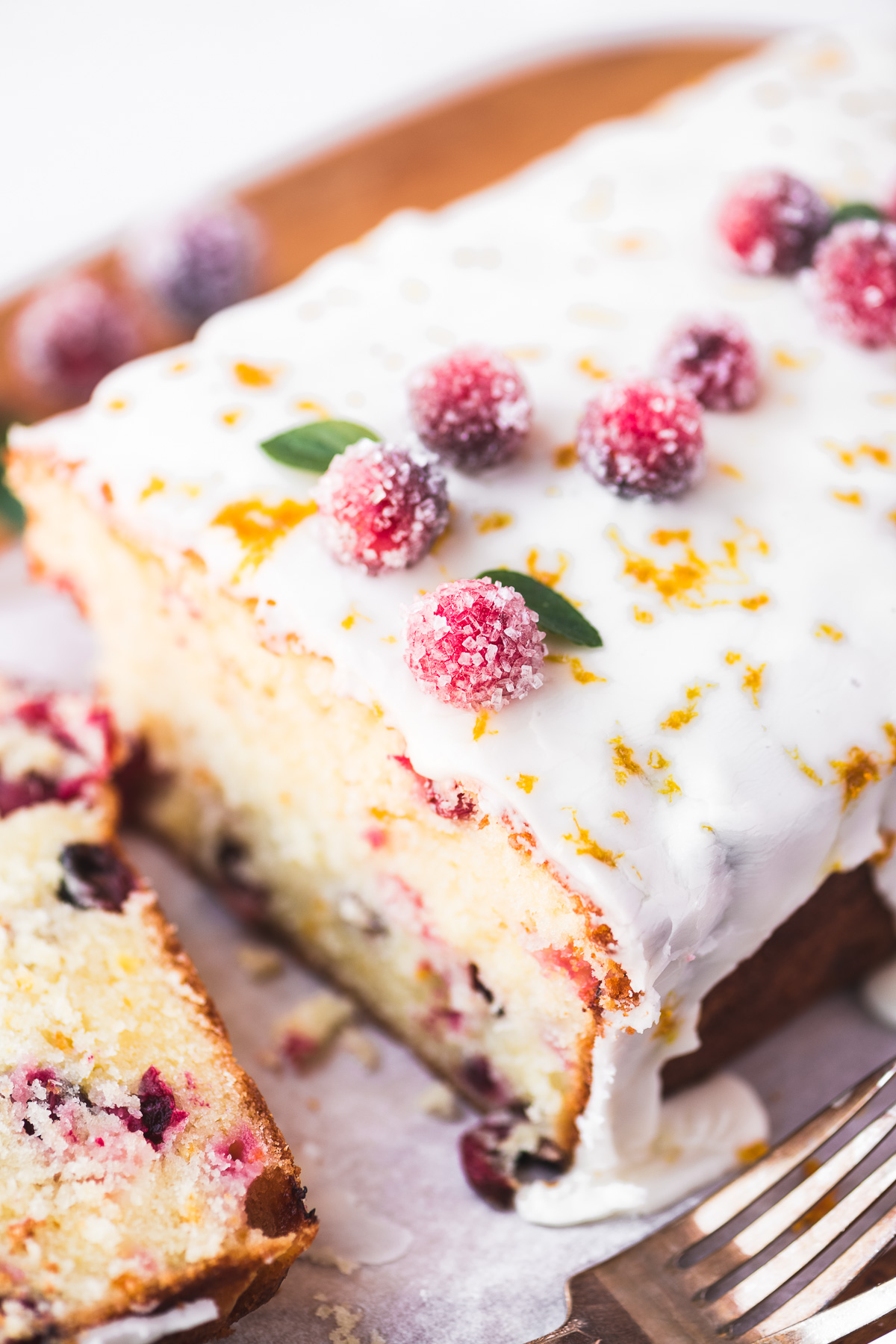 Cranberry orange loaf cake topped with sugared cranberries.