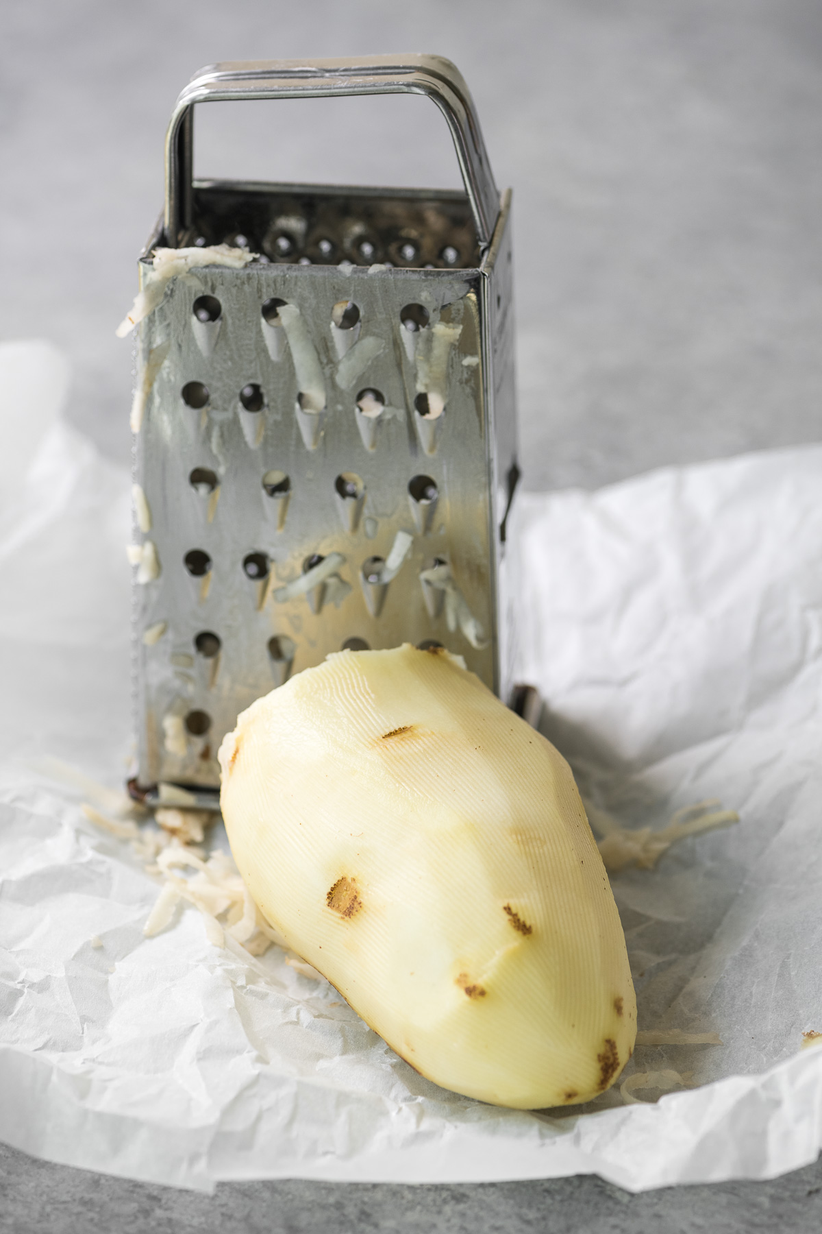 grating a potato on a box grater