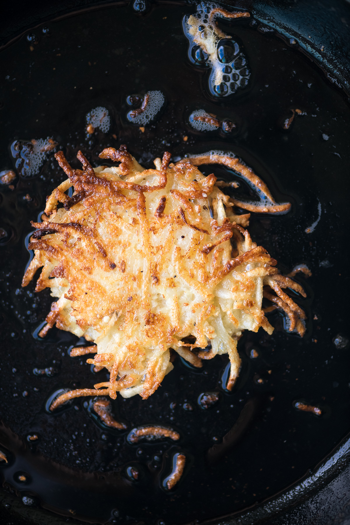 frying potato latkes in a cast iron skillet