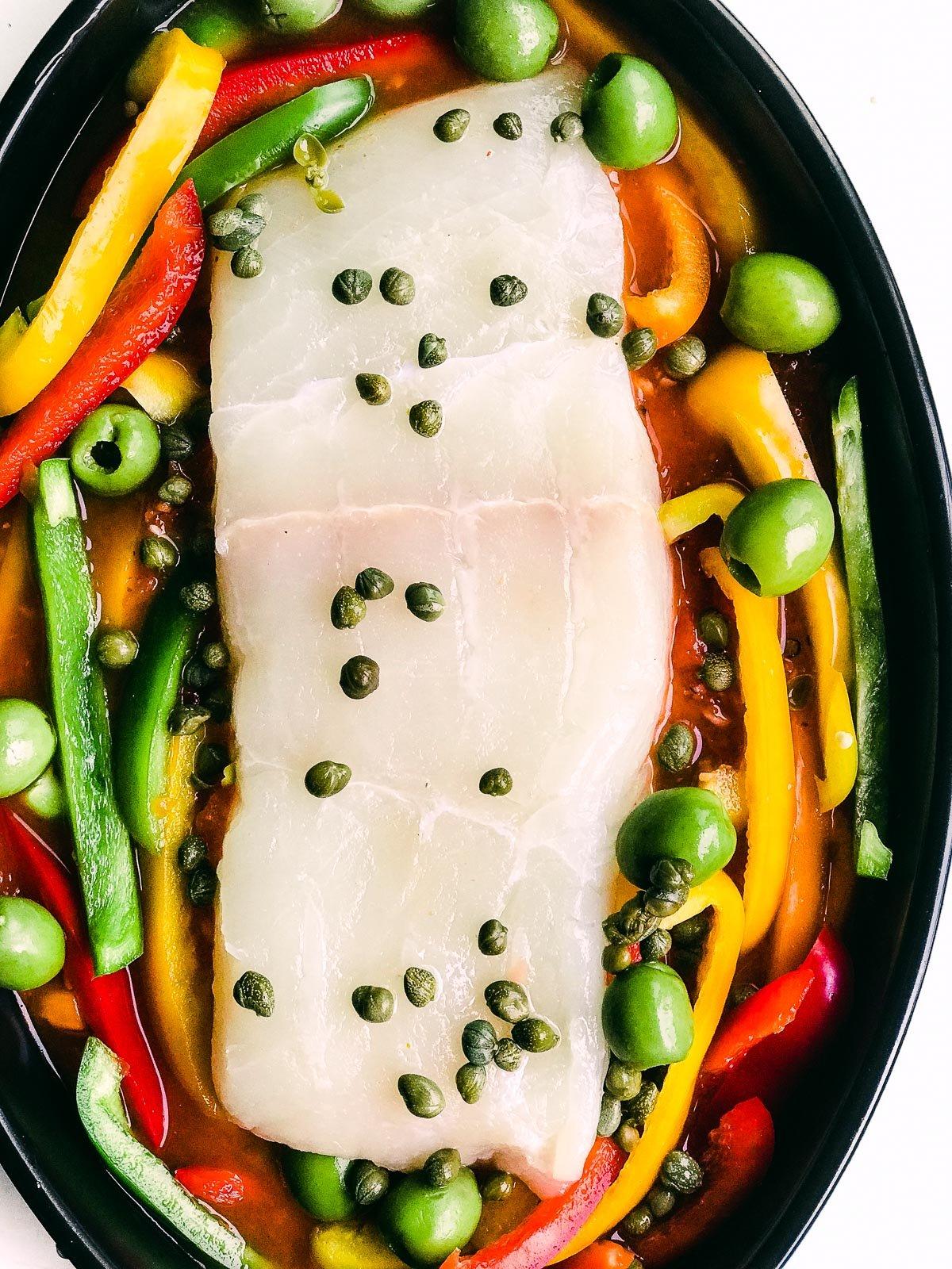 assembling roasted halibut with Mediterranean veggies
