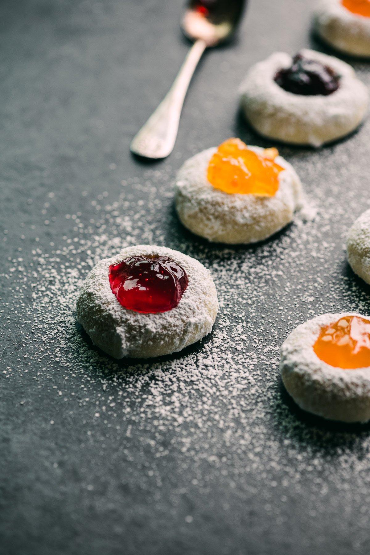 jam thumbprint cookies on a dark ground