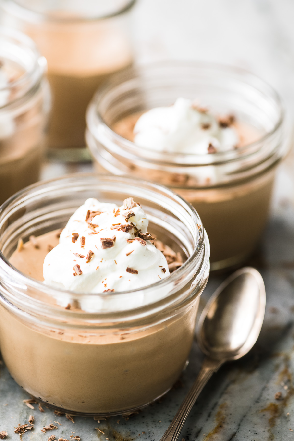jars of milk chocolate mousse with whipped cream and chocolate shavings