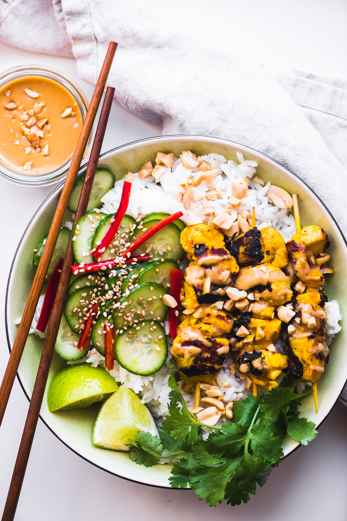 chicken satay bowl with chopsticks and peanut sauce
