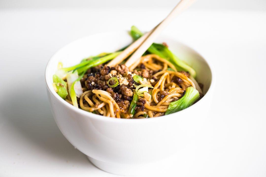 a bowl of dan dan noodles on a white table