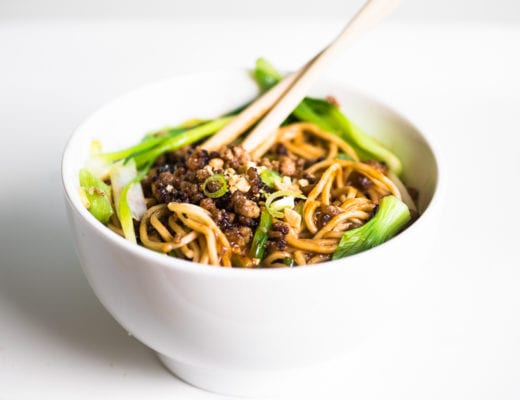 a bowl of dan dan noodles on a white table