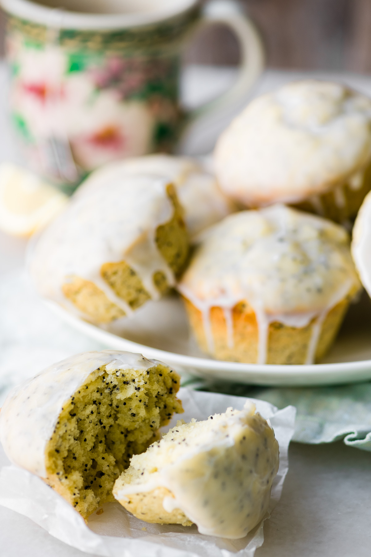 lemon poppy seed muffins on a plate with cup of tea