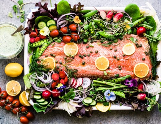 spring salmon salad on a white platter with fresh veggies