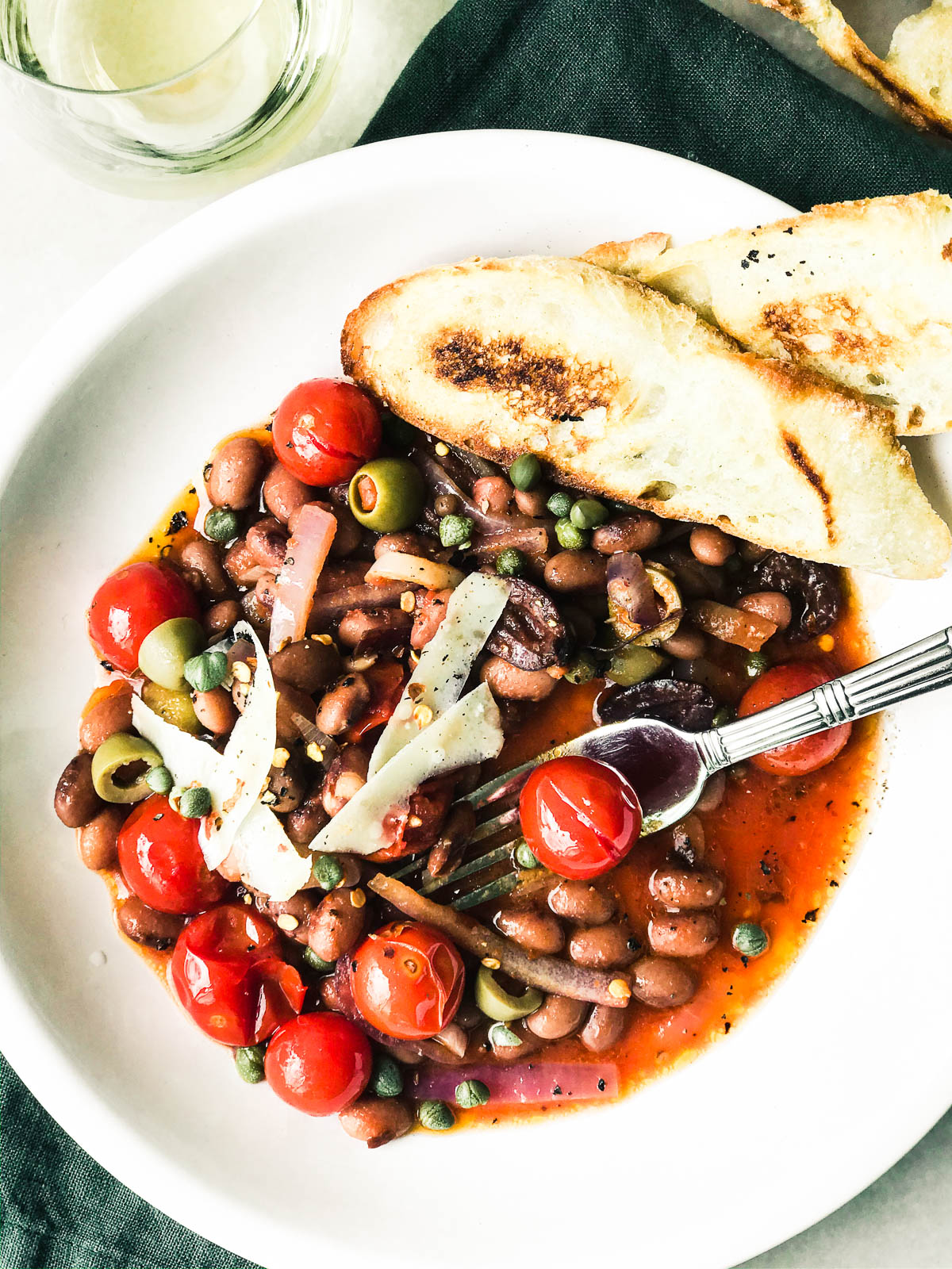 Beans Puttanesca with toast, in a white bowl