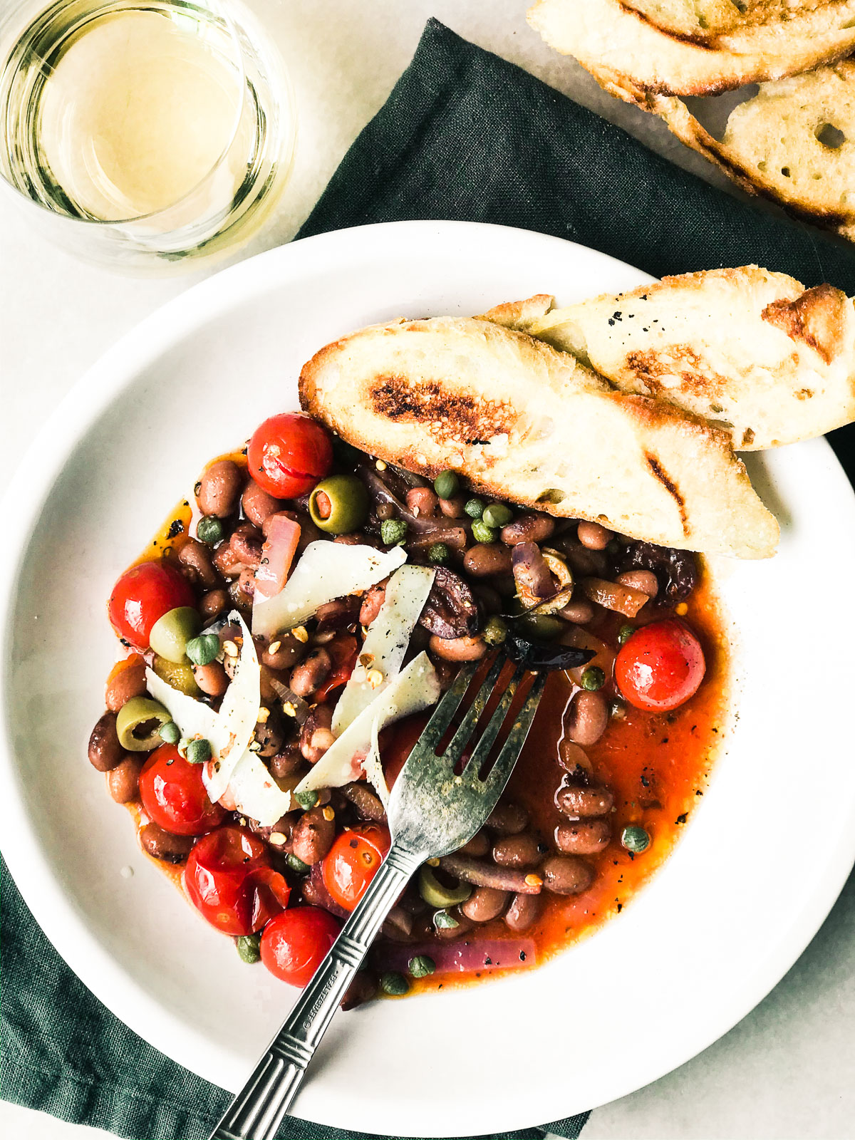 Beans Puttanesca in a white bowl with toast