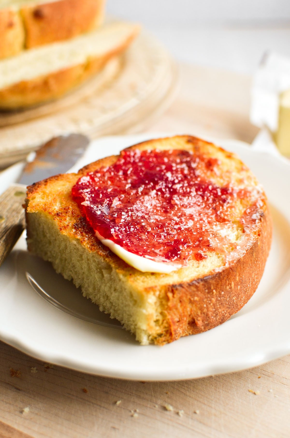 A slice of homemade bread with butter and jam.