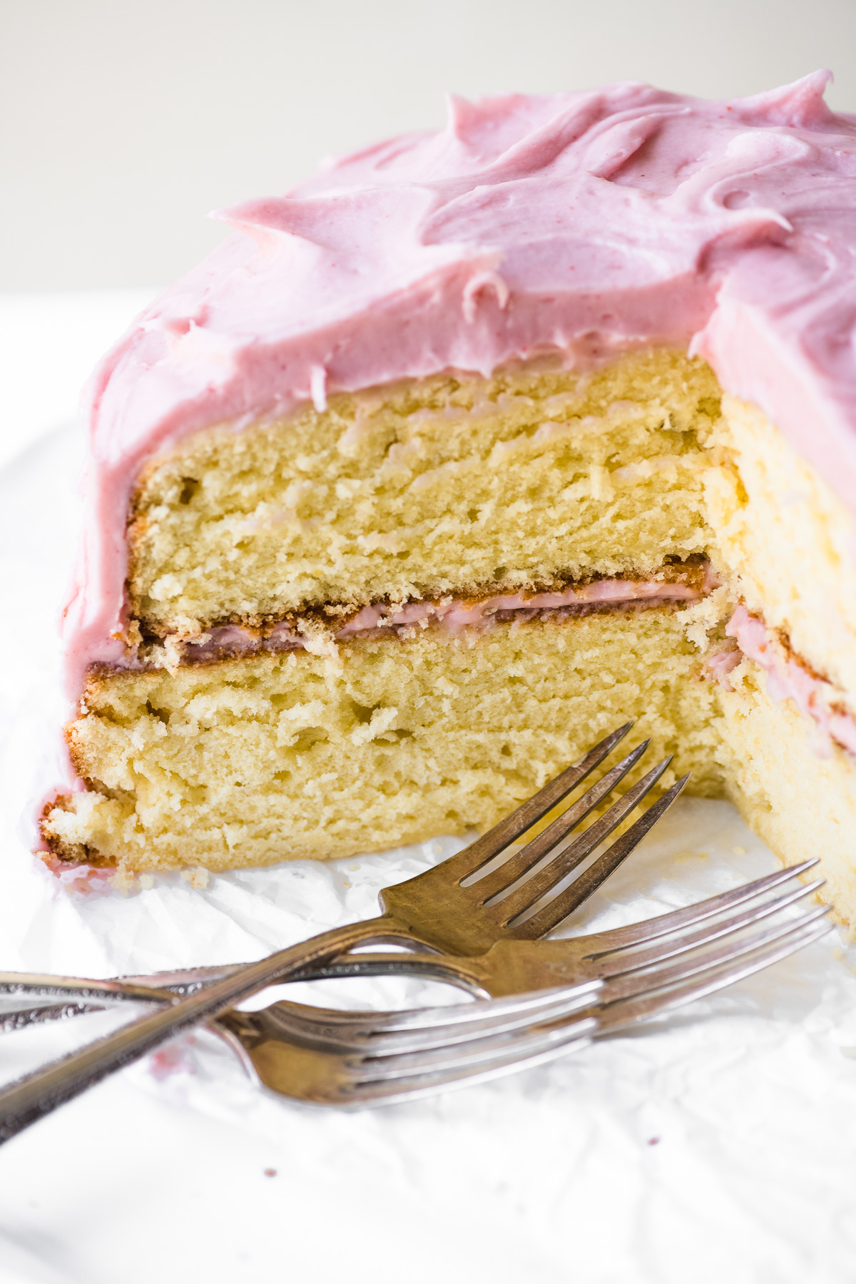 a yellow cake with strawberry frosting, cut open