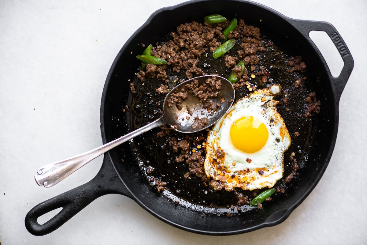 Korean beef in a skillet with a fried egg