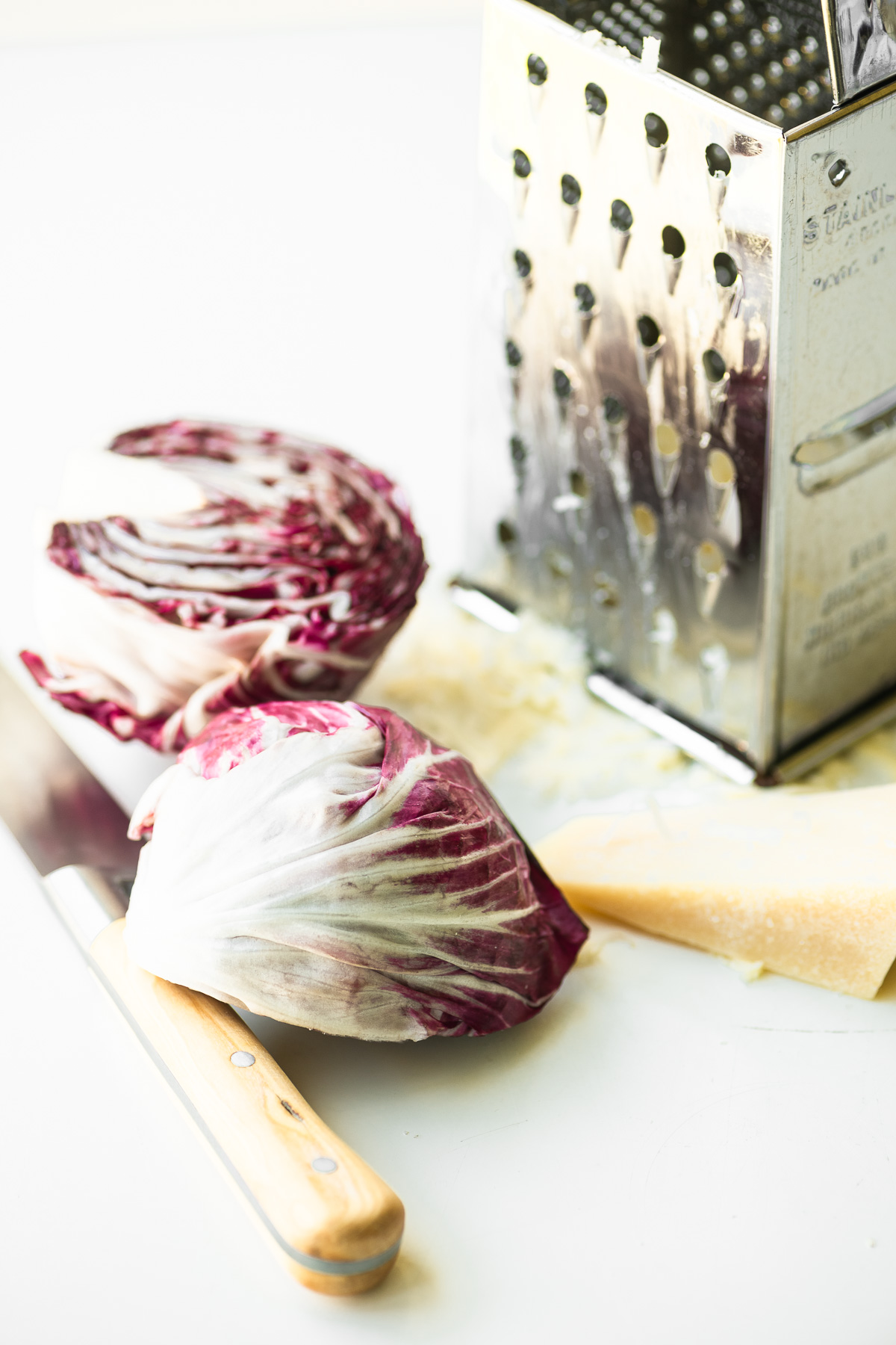 grating cheese with a head of radicchio