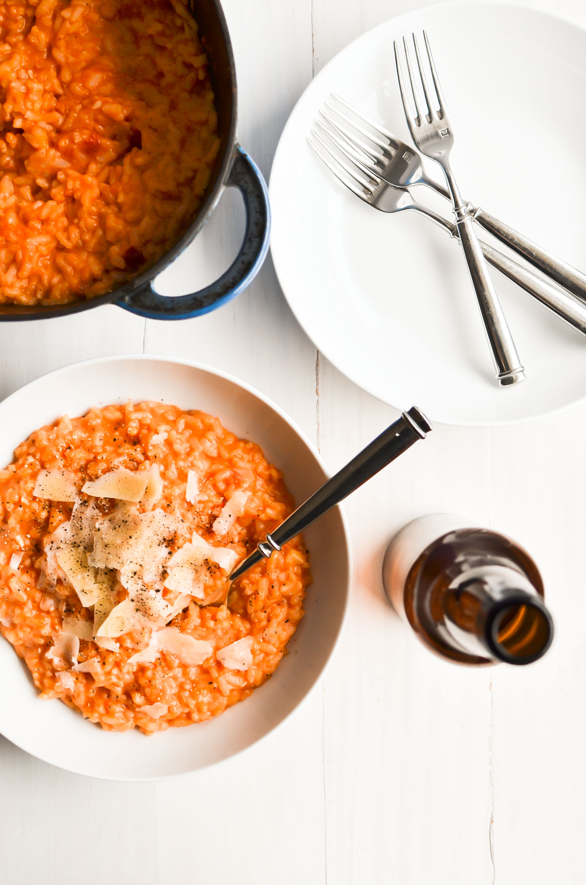 a bowl of tomato risotto with pan, plate, and forks