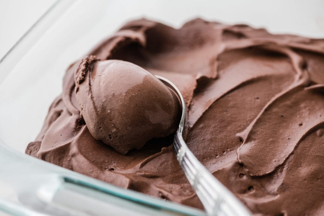 scooping chocolate frozen custard with a spoon