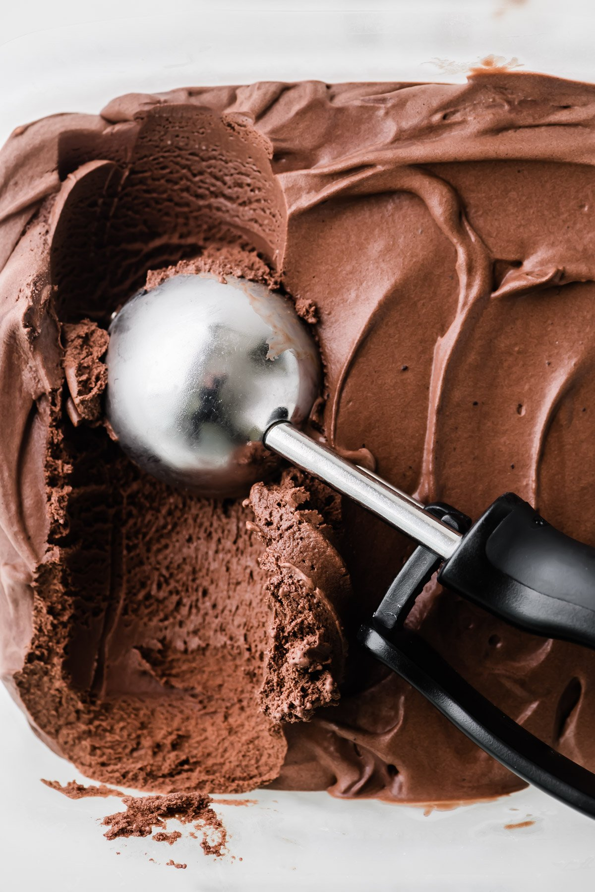 scooping chocolate frozen custard with an ice cream scoop