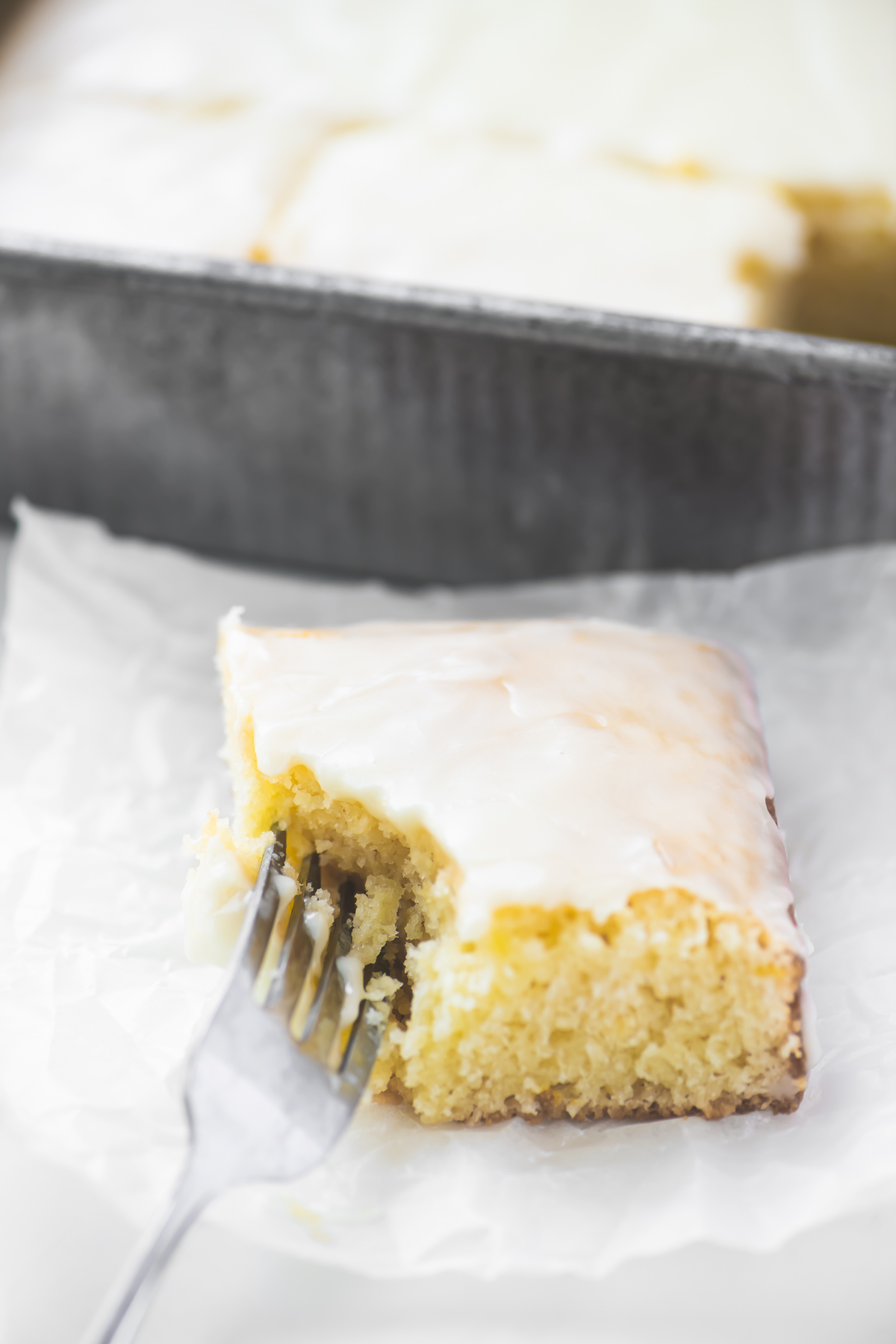 A piece of lemon velvet sheet cake with fork