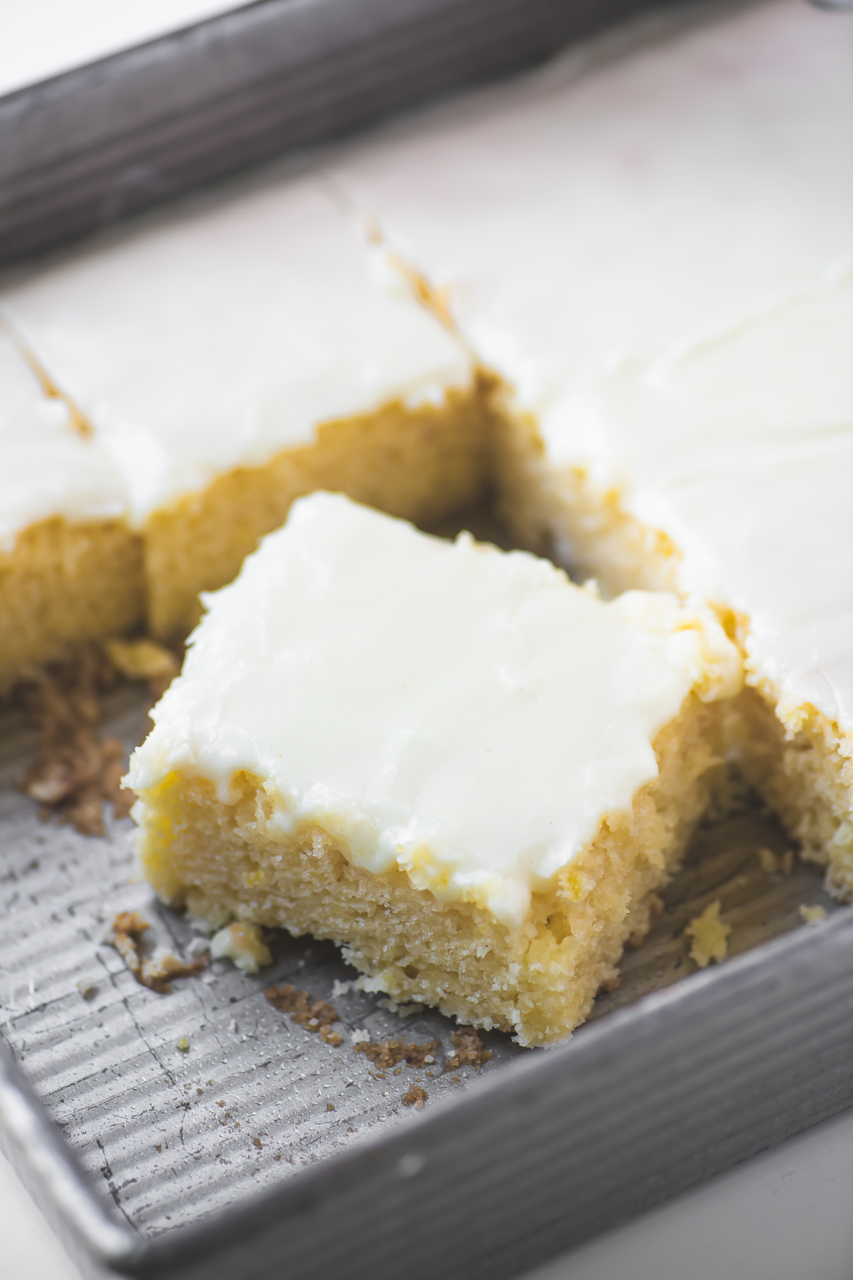 cutting squares of lemon velvet cake in the pan