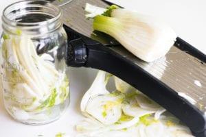 slicing fennel on a mandoline slicer