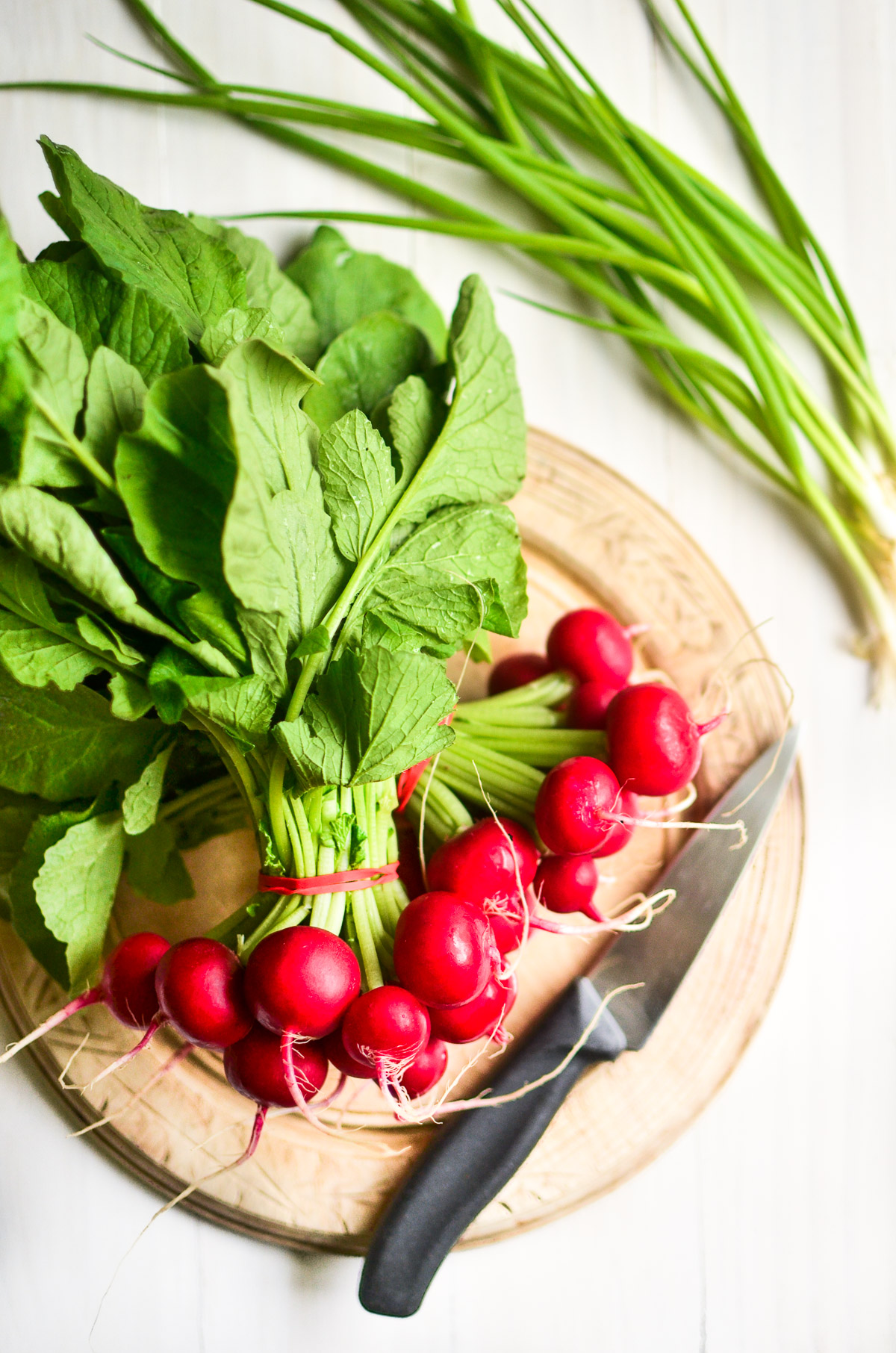 A bunch of fresh red spring radishes on a cutting board with a knife