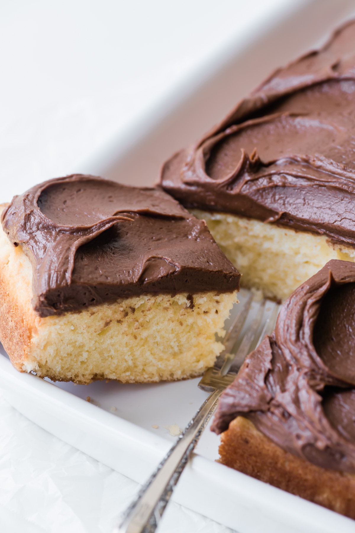 cutting a piece of yellow cake with chocolate frosting