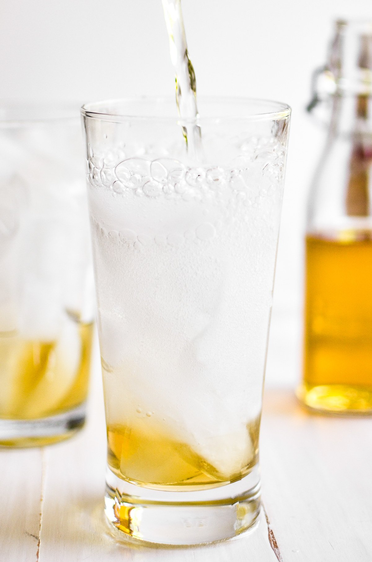 pouring seltzer water over vanilla syrup to make homemade cream soda