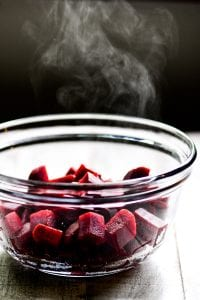 Chopped beets, steaming, in a glass bowl