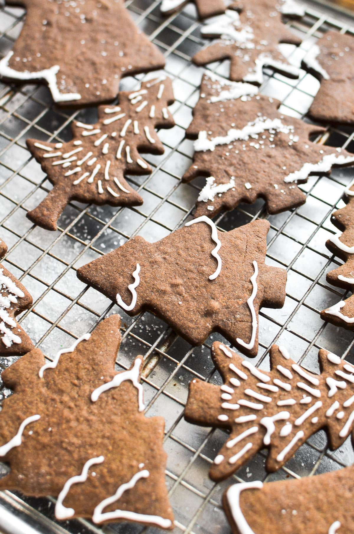 Decorated gingerbread tree cookies on a baking rack.