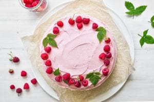 Raspberry layer cake topped with raspberries and raspberry leaves.