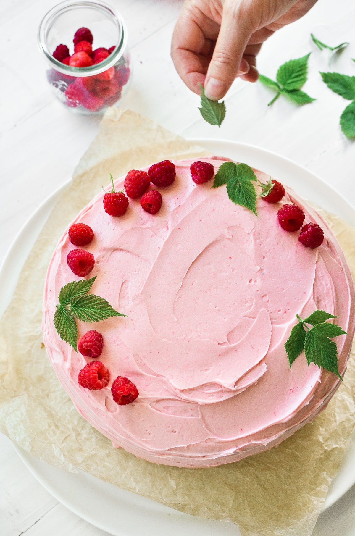 Topping a raspberry layer cake with raspberries and raspberry leaves.