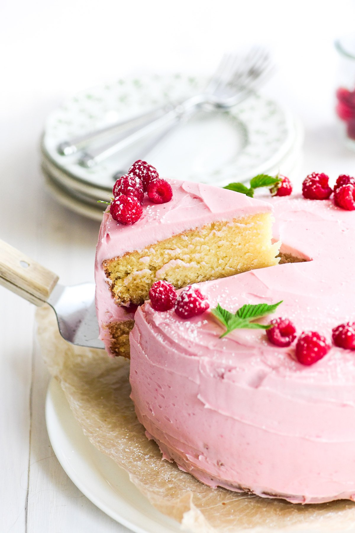 A slice of raspberry layer cake being served.