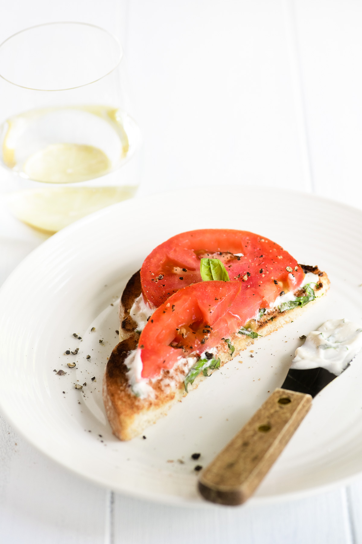 tomato toast with basil mayo and a glass of water