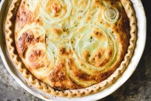 Vidalia Onion Pie in a white pie dish on a baking sheet