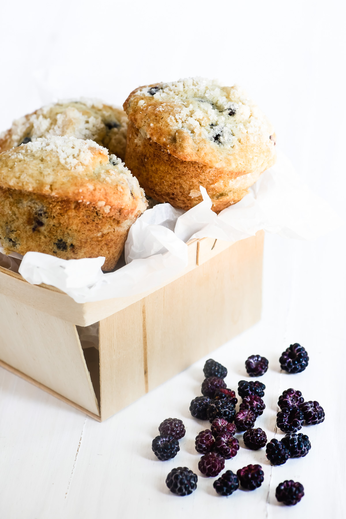 black raspberry muffins in a basket with fresh berries