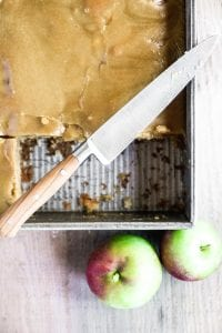 caramel apple cake with glaze, in pan with knife