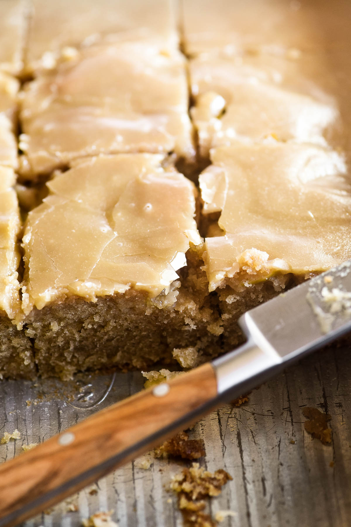 Caramel apple sheet cake in the cake pan, sliced into pieces.