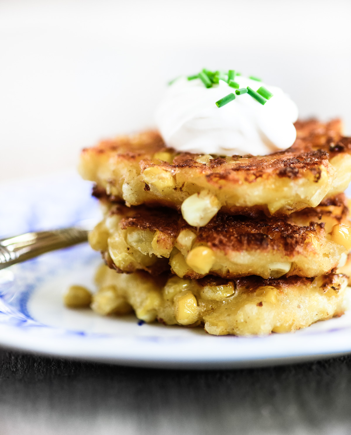A stack of buttermilk corn fritters on a small plate