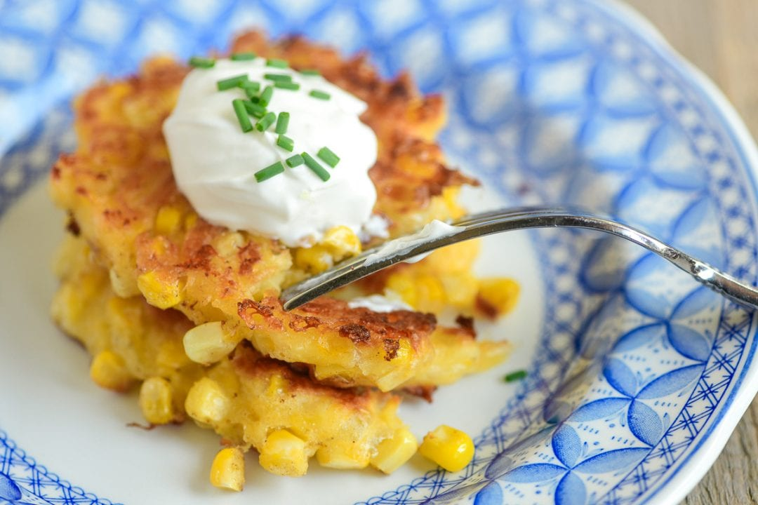 Taking a forkful of corn fritters topped with sour cream and chives