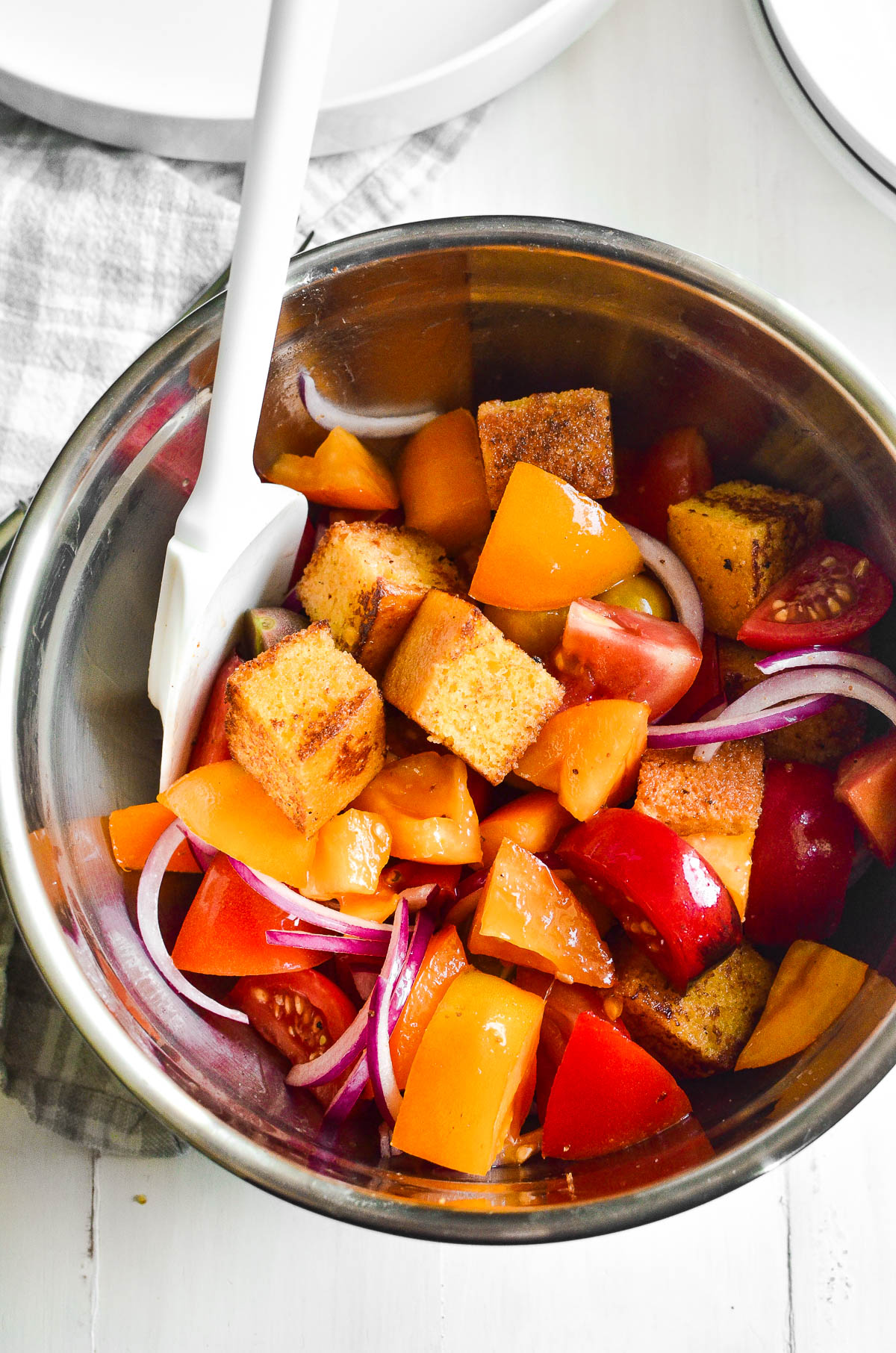 Mixing cornbread panzanella ingredients in a stainless steel mixing bowl with a white spatula.