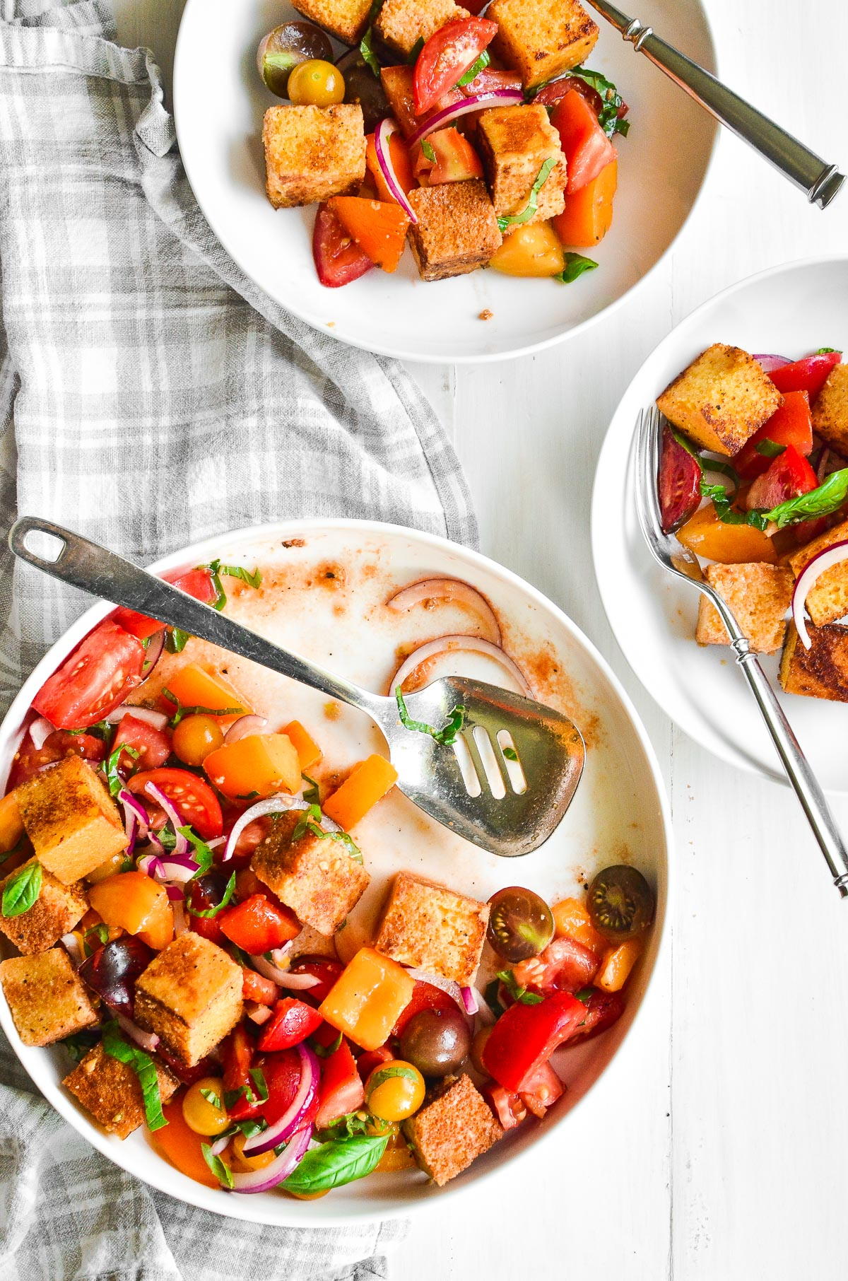 A platter of cornbread panzanella with a serving spoon and two white bowls of panzanella with forks.
